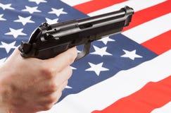 在手中开枪与在背景-美利坚合众国的旗子 免版税库存照片