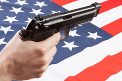 在手中开枪与在背景-美国的被翻动的国旗 免版税库存图片
