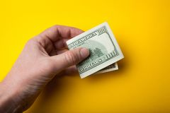 在手中弯曲一百元钞票在黄色背景、销售或者购买 库存照片