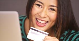 在手中微笑与卡片的愉快的妇女 免版税库存照片
