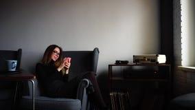 在手中微笑和摆在照相机的引人入胜的少妇,与电话,坐在时髦的咖啡馆的灰色扶手椅子  股票视频