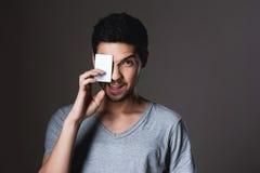 在手中微笑在与信用卡的灰色背景的一个正常男孩的画象 免版税库存照片