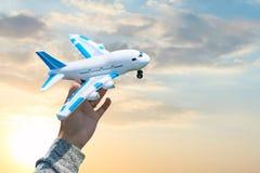 在手中戏弄塑料飞机反对蓝天和日落 梦想、假期或者旅行概念 葡萄酒定了调子作用 免版税库存图片