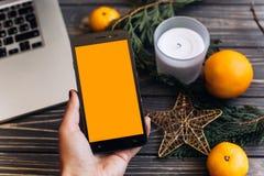 在手中打电话与空的屏幕在绿色圣诞节背景  库存照片