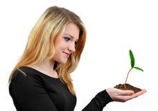 在手中拿着增长的植物的女孩 库存图片