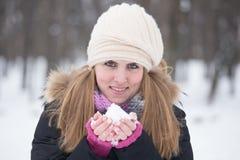 在手中拿着雪的一俏丽的少女和看照相机 库存照片