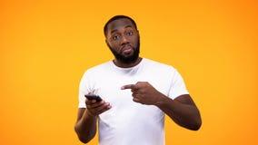 在手中指向智能手机的年轻美国黑人的人,推荐应用 免版税库存照片