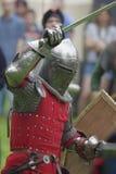 在手中授以爵位在有剑的钢装甲并且保护 库存图片