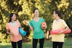 在手中摆在有瑜伽席子的一个公园的三个怀孕的女孩 他们微笑并且获得乐趣 图库摄影
