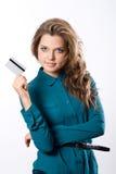 在手中显示信用卡的美丽的友好的女孩 免版税库存照片