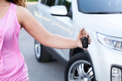 在手中显示点火开关的无法认出的妇女在自己新的汽车附近 库存照片