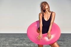 在手中晒日光浴在海滩桃红色可膨胀的圈子的女孩 库存照片