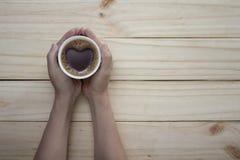 在手中爱有心脏形状的咖啡杯在桌上 免版税图库摄影