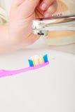 在手中牙刷的牙膏,在卫生间水槽 免版税库存图片