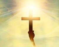 在手中现出轮廓十字架,在光的宗教在日出的标志和风景 免版税库存照片