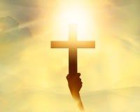 在手中现出轮廓十字架,在光的宗教标志和风景 免版税库存图片