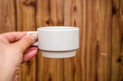 在手中白色杯子在木背景 免版税库存照片