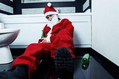 在手中睡觉在有啤酒瓶的卫生间的酒醉圣诞老人 库存图片