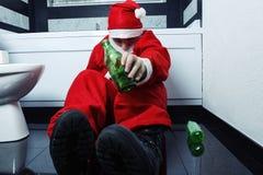 在手中睡觉在有啤酒瓶的卫生间的酒醉圣诞老人 免版税库存照片