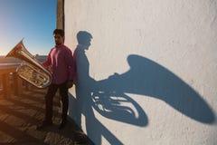 在手中站立与喇叭的年轻人,在白色墙壁上的一个大阴影 免版税库存图片