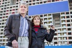 在手中站立与房子钥匙的资深夫妇反对在大厦的蓝色空白的横幅 免版税库存照片