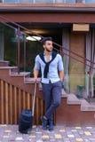 在手中站立与手提箱和p的可爱的年轻阿拉伯人 库存照片