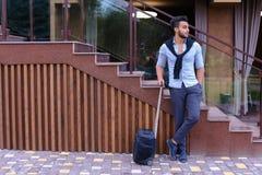 在手中站立与手提箱和p的可爱的年轻阿拉伯人 免版税图库摄影