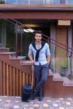 在手中站立与手提箱和p的可爱的年轻阿拉伯人 库存图片