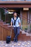 在手中站立与手提箱和p的可爱的年轻阿拉伯人 免版税库存照片