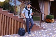 在手中站立与手提箱和p的可爱的年轻阿拉伯人 免版税库存图片