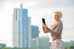 在手中站立与电话的女商人 免版税库存图片