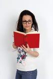 在手中站立与红色书的ABeautiful少妇 工作室 免版税库存照片