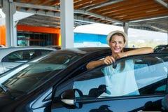 在手中站立在有b的钥匙-概念的一辆汽车附近的愉快的妇女 库存照片