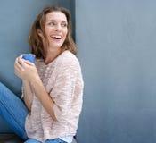 在手中笑与一杯咖啡的愉快的妇女 库存图片