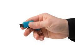 在手中蓝色USB棍子,隔绝在白色 库存照片
