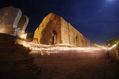 在手中被点燃的蜡烛在寺庙附近。 免版税图库摄影