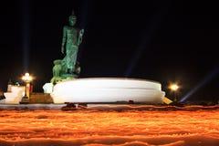 在手中被点燃的蜡烛在菩萨雕象附近 库存图片