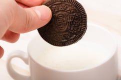 在手中被隔绝的OREO饼,在牛奶的扣篮 免版税库存图片