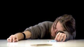 在手中说谎在与注射器的桌上的不自觉的女性少年,毒瘾 免版税库存图片