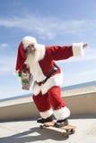 在手中踩滑板与礼物的圣诞老人 免版税库存图片