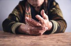 在手中遭受痛苦的年长妇女 关节x线照片 库存图片