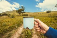 在手中金属化杯子用茶一次远足的一个游人在山在白色云彩下 库存照片