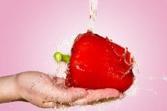 在手中飞溅与红辣椒在桃红色背景 库存照片