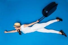 在手中飞行有准备好的行李的旅行妇女旅行在蓝色背景 免版税图库摄影