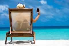 在手中说谎在与移动电话的一个海滩懒人的女孩 免版税库存照片