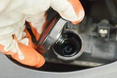 在手套开放汽车幅射器盖子和检查水平面的手安全 免版税库存照片