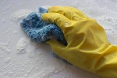 在手套的一只女性手洗涤与一块旧布的表面与泡沫 大扫除概念 库存照片