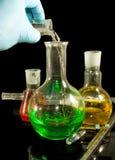 在手套的一只手和在一个黑背景特写镜头的实验室玻璃器皿 图库摄影
