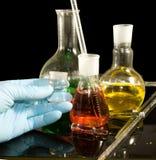 在手套的一只手和在一个黑背景特写镜头的实验室玻璃器皿 库存照片