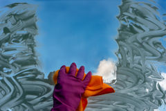 在手套的一只手洗涤窗口 免版税库存图片
